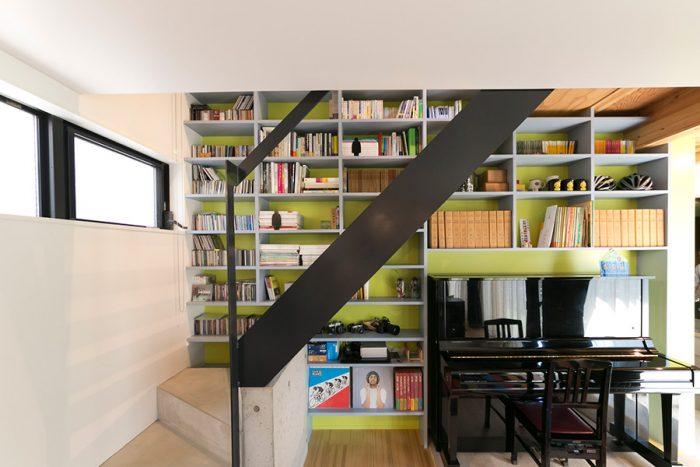本棚のグリーンの壁が、1階から2階へと連続している。コンクリートの塊と黒の階段の手摺りが空間のアクセントになっている。