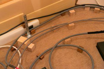 ケーブルを床に直接置かない、オーディオマニアのこだわり。木のブロックをかませてケーブルを持ち上げている。