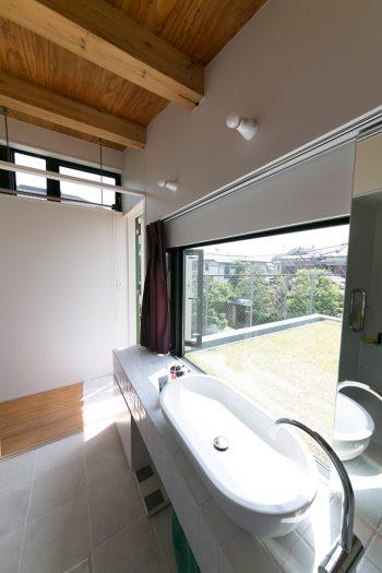 2階の明るい洗面所。ガラス越しに、屋上緑化のグリーンが見える。眺めを妨げないよう、洗面鏡は引き戸に。