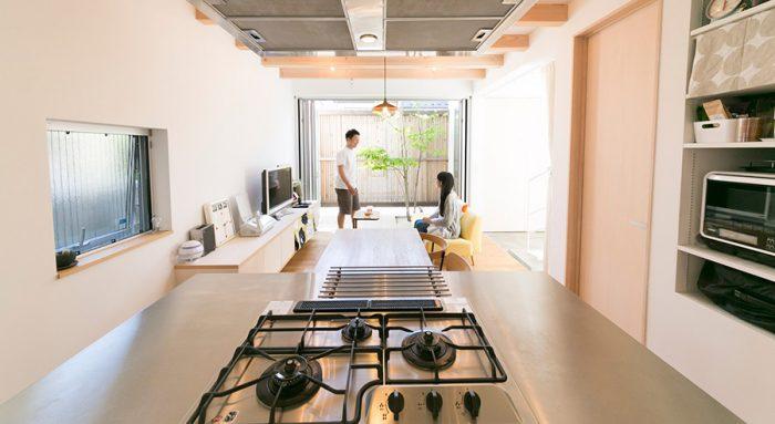 キッチンから中庭を見る。木製ルーバーまでの距離が長く、リビングが広々と感じる。