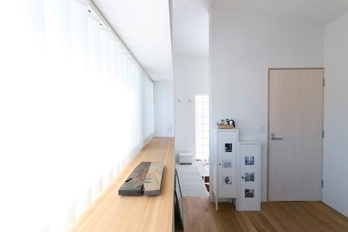 2階の寝室。ドアはシナ合板に白色の拭き取り塗装し、白い壁になじむようひと手間を加えた。出窓も広く見せるポイント。