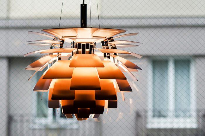 ルイス・ポールセンのペンダントライト「アーティチョーク」。微妙にカーヴした羽が描く美しい間接光が印象的。一台を生産するのに20人以上の熟練工の手が必要と言われており、クラフツマンシップの技術が宿る。外側は銅のヘアライン仕上げ、内側は良質な反射板を得るため、つやの度合いを抑えた塗装が施されている。