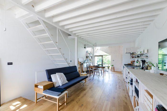 2階のLDKスペース。床の木の色と壁の白色がベースとなった中でソファの藍色が映える。