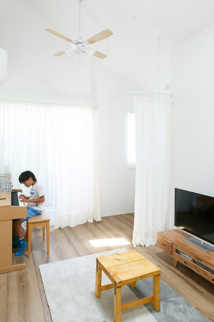 2階のリビング。夜は奥のカーテンを閉め、夫妻の寝室としている。テレビ前のテーブルはDIYでつくったもの。