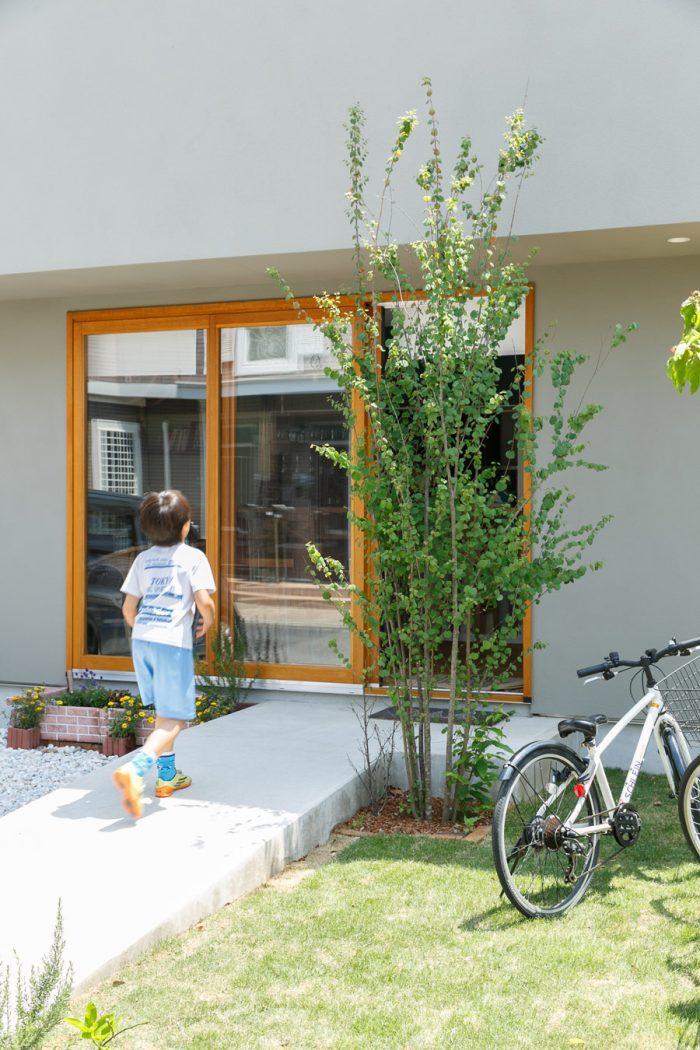 バリアフリーのエントランス。家の前の芝生で遊んでいた小学校4年生の息子さんはサッカーと日本史に夢中だそう。「リフティングの記録は61回! 好きな時代は安土桃山!」と元気いっぱいに教えてくれた。