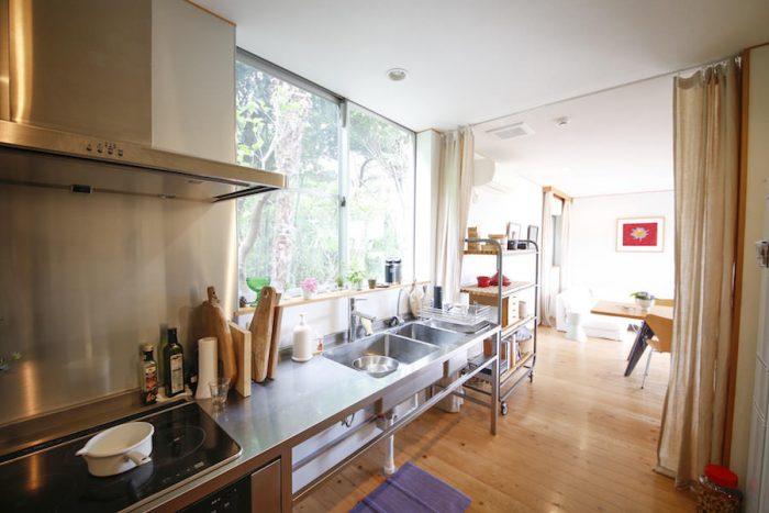 裏庭の緑がまばゆいキッチン&ダイニング。硬質なステンレスと、モダンな家具やアートが映える。
