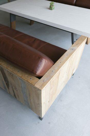 廃材を使ったオリジナルのソファ。木目のFRP素材のテーブルはアートユニット『ゲルチョップ』のもの。