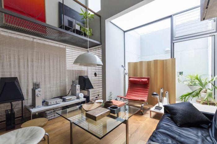 コンパクトな中で家具がうまく配置されたコージーな空間。ソファやイージーチェア、スクリーンはデンマークのポール・ケアホルムによるデザイン。