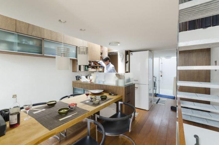キッチンではダイニングに座る人と話をしながら作業ができる。ダイニングの手前側のスペースは廊下を兼ねることによって寸法を詰めている。