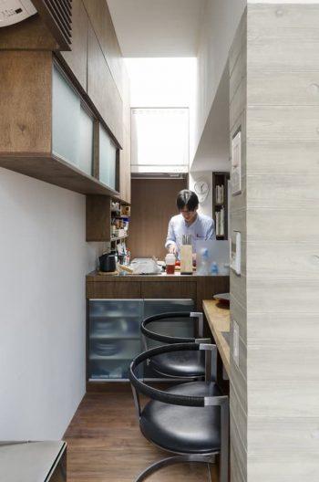 トップライトから光が落ちるキッチンは手を伸ばせばすべて届く最小寸法。ダイニングのチェアはカストホルム&ファブリシャス。