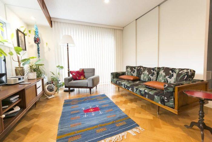 迷彩柄とラタンを組み合わせたソファー、テレビボードは「HOUSETRAD」オリジナル。天井は立体感が出るようソーラトンを採用。