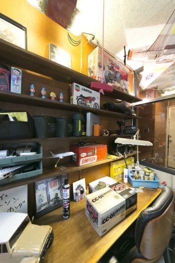 仕事場としても使うガレージの机と棚は、水野さんがDIYで。作ったラジコンが宝のように飾られている。