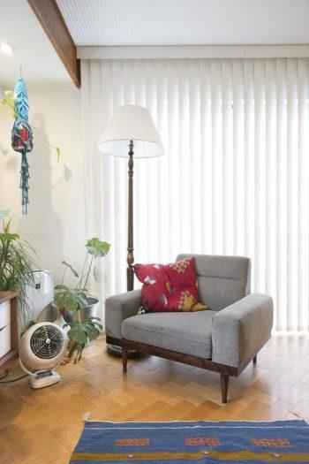 縦型のブラインドから入る光が陰影を出す。ソファー上のクッションで赤をさし色に。