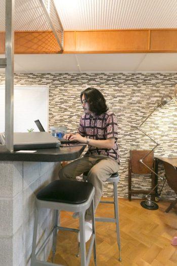 「HOUSETRAD」代表の水野さん。キッチン脇の小さなカウンターテーブルは、同社のおすすめスタイル。