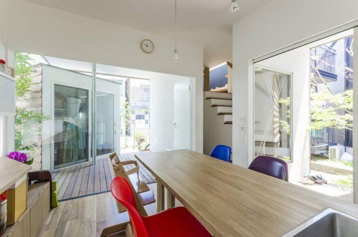 ダイニングキッチンから家の正面側を見る。いろいろな方向で視線がすっと外へ抜けていく。そしてその先には緑が見える。外に見えるのはMさんの趣味部屋。