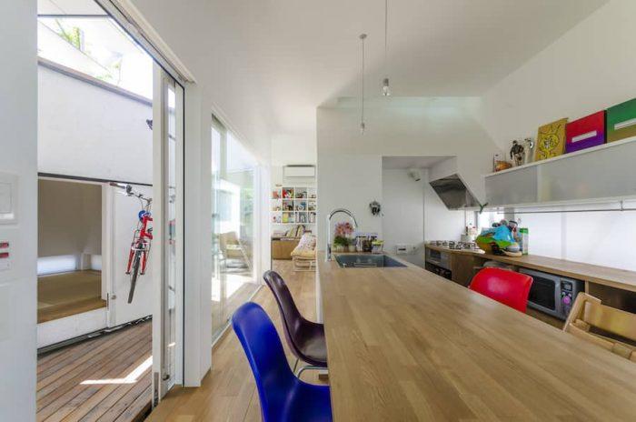 ダイニングキッチンのスペースから奥にリビングを見る。左は分棟としてつくられた和室。