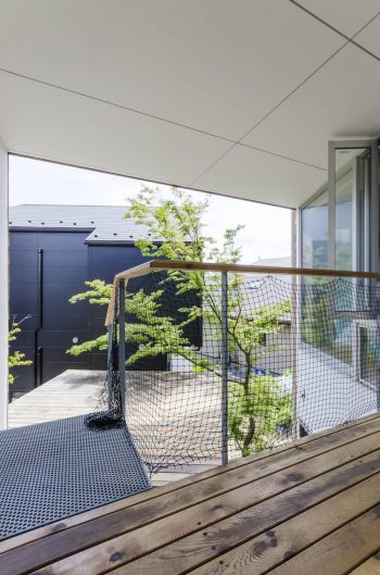 2階の和室と子ども部屋をつなぐ廊下から、分棟になっている和室の屋根のデッキを見る。