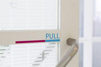 """玄関ホールとリビングの間の扉。""""PULL""""のカッティングシートの色づかいが、インテリアのトーンにもマッチしている。"""