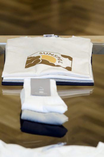アーカイブのロゴをプリントしたTシャツは表参道店限定のカラーを用意。手前はオールシーズン展開しているエジプト綿で作られたソックス。