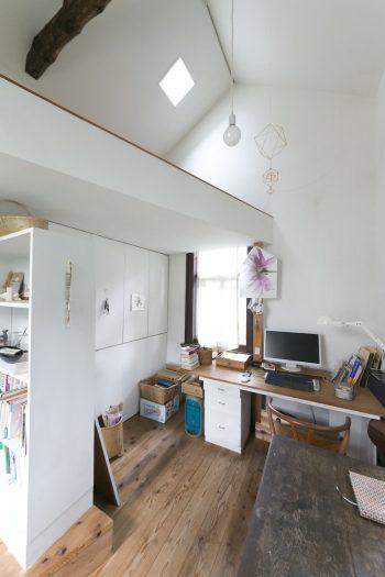 2畳半の中2階の下は造り付けの収納に。シナ合板の本棚には設計士・福原正芳氏と一緒にペンキを塗装した。