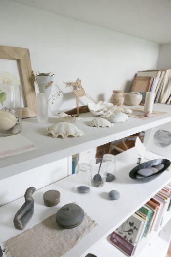 本棚は後ろの板の一部分をあえて外して、抜けを出した。アーティストの作品や拾った貝殻、弥生時代の須恵器などが飾られる。