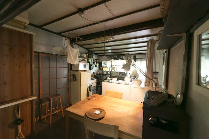 穏やかなあかりが灯る台所。仕切りともなっている棚は配膳台にも。テーブルはウレタン塗装を剥がして使用。