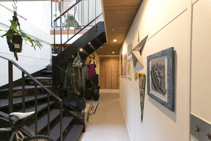 タイル敷きの床に鉄骨の階段が、インダストリアルな雰囲気。基礎を温める蓄熱設備を採用し、冬も床からじんわりと暖かい。