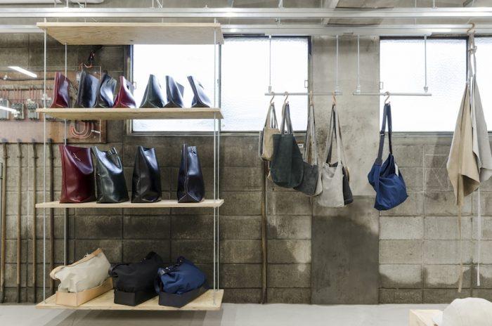 バッグコレクションのコーナー。左側の上段と中央は牛革を使用したノットエコバッグシリーズ。中央のS字フックにかけられているのがピッグレザーのバッグ。一番右にかけられているのはピッグレザーのエプロン。