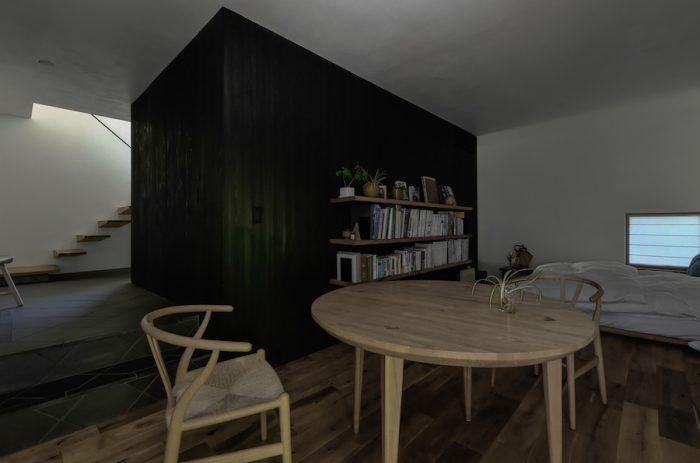 2階とは対照的なしっとりと落ち着いた暗さが特徴の1階北側の空間。黒い壁に囲まれた部分には、ウォークスルークローゼットとトイレ、収納が入っている。