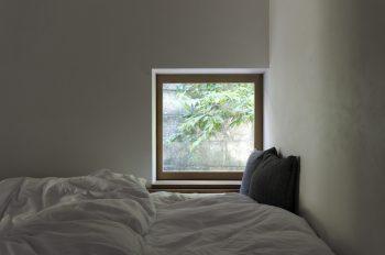 ベッド脇の開口が隣家の緑をちょうどいい具合にフレーミングしている。