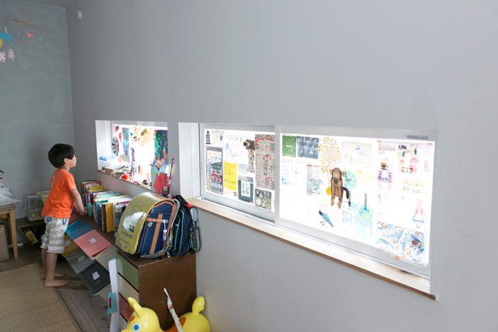 窓ガラスに晴生くんの作品やお気に入りのフライヤーをペタペタ。ギャラリー兼カーテンの出来上がり。