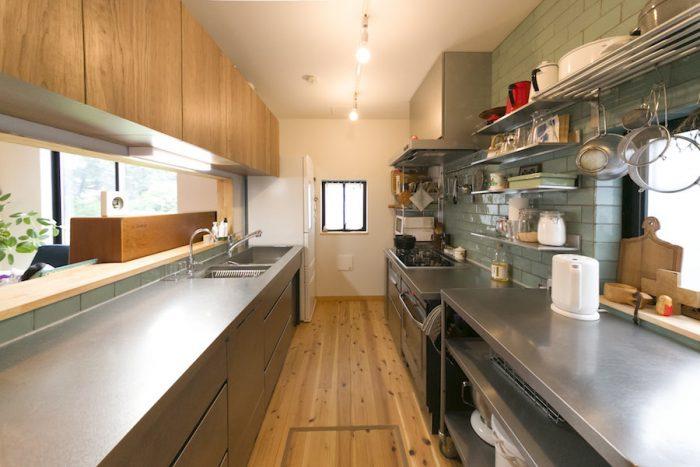 オールステンレスに薄いグリーンのタイルが映えるキッチン。吊り戸棚には悩んだ結果、玄関用収納棚を活用した。