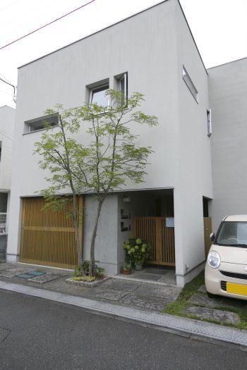 白い壁に木製のドアがモダン。1階はご両親の居住スペース。