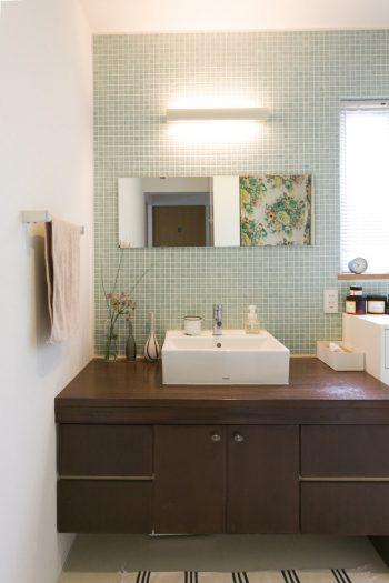 洗面所だけは少し雰囲気を変えて、スペインのガラスモザイクをセレクト。シンクは木で造作してもらった。