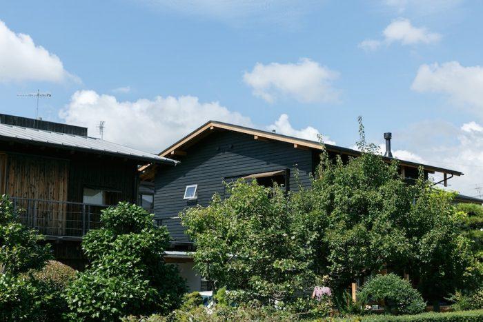 さきたまの家外観。外壁の黒と庭の緑のコントラストが目を引く。左に建つのは、10年前に建てた「かねこ建築製作所」のアトリエ。