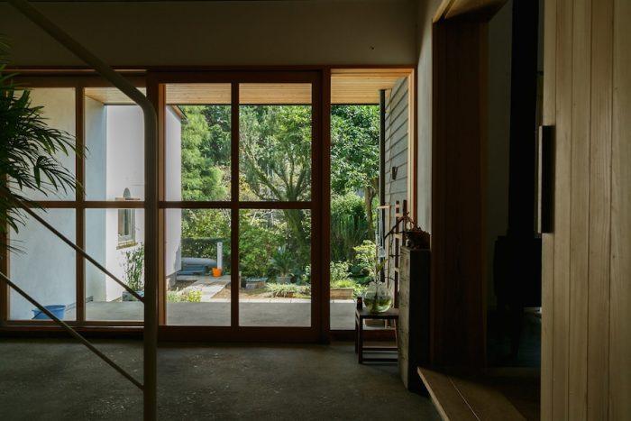 玄関から外を見る。ガラス張りの引き戸を通して、外とのつながりが感じられる