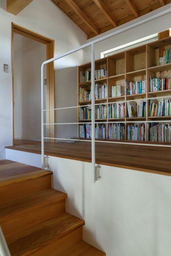 階段を上がった先には、大容量の家族の本棚。