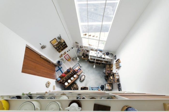 2階の畳スペースとフローリングのレベル差でできた隙間からお店部分を見下ろす。吊り下がるライトは、塚本さんがオリジナルでつくってもらったもの。