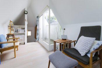 2階の畳側から階段のほうを見る。家具やクッションが北欧テイストでまとめられている。