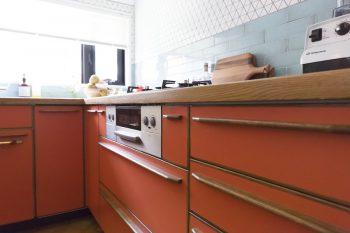 オレンジ色の扉や、レトロ感のある色の木の把手など、ミッドセンチュリーなデザインのキッチンは、特注で作ったオリジナル。