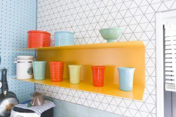 キッチンの色の組み合わせがとてもカワイイ。三角の白のタイルと薄いブルーの長方形のタイル、有孔ボードも水色。