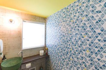 トイレの壁の三角形のタイル。ところどころに黄色を配したカリフォルニアらしい色使い。壁には古材。