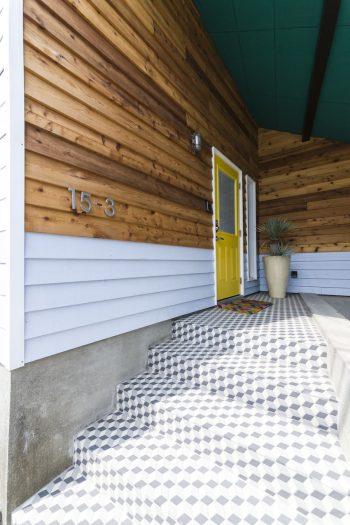 2トーンの板張り、下の部分はスカイブルー。幾何学模様のタイルと黄色いドア。天井はグリーン。カリフォルニアを感じさせる配色。