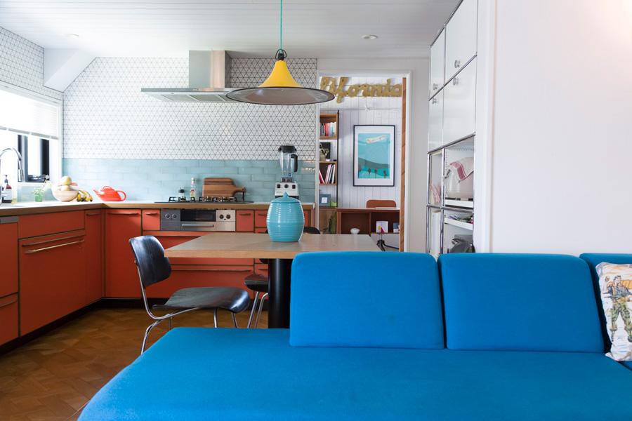 ソファーのブルー、キッチンのオレンジ、イエローの照明器具のシェード……ミッドセンチュリーな色の組み合わせのセンスが抜群。