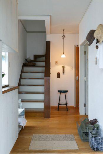 玄関から室内を見る。漆喰塗りの壁に、小物のディスプレイが映える。写真左の靴箱も、「アローズ」にオーダーしたもの。塗料を塗る/削るを繰り返して独特の風合いをつくっている。
