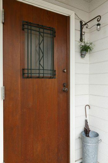 玄関扉も「アローズ」でオーダー。木と鉄とガラスを組み合わせ、古いドアノブをつけて、古建具のような雰囲気に。外壁は既存のままだが、玄関ドアを替えるだけで、家の印象が大きく変わる。
