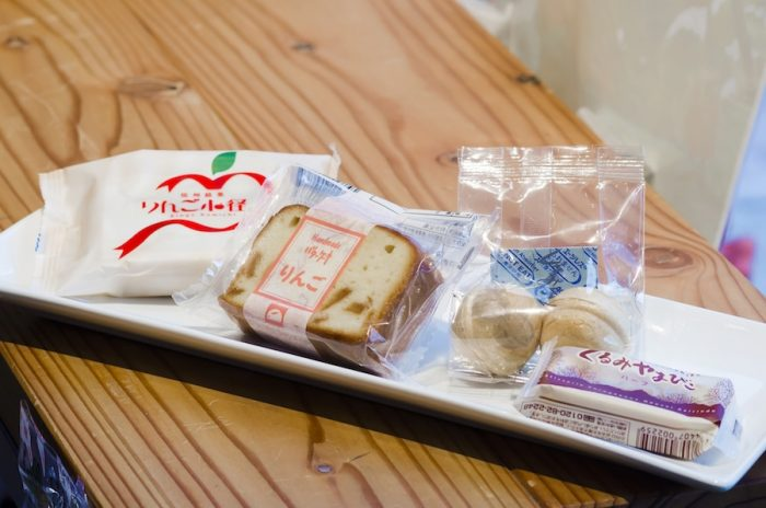 長野県産のりんごやくるみを使ったお菓子も豊富。(左から)菓子の銘菓「二葉堂」の「りんご小径」は完熟りんごの果実煮をやわからいクーヘン生地でサンドし、それをホワイトチョコレートでコーティングしたスイーツ。「信濃路うさぎや」の「りんごケーキ」は刻んだりんごをたっぷりと入れてしっとりと焼き上げたバターケーキ。「花岡」の「くるみ最中」はくるみが入ったキャラメル風味の餡がたっぷり。「ヌーベル 梅林堂」の「くるみやまびこ」は八ヶ岳山麓でとれる新鮮な牛乳を使ってじっくり煮込んだ特製くるみキャラメルをサクサクのクッキーで包んだもの。