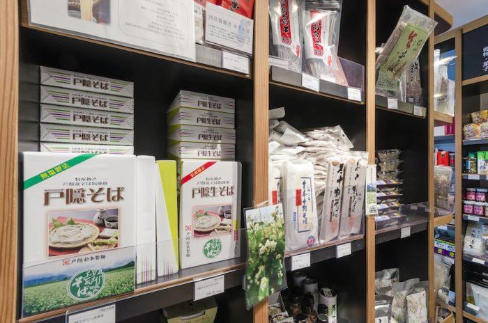 1階にはさまざまな蕎麦商品が並ぶ。日本三大蕎麦の一つ「戸隠そば」は、山菜のてんぷら、すりおろした大根を薬味に用いるのがスタイル。そのほか、濃縮された麺つゆがついた生そばや、半生そばもラインナップ。