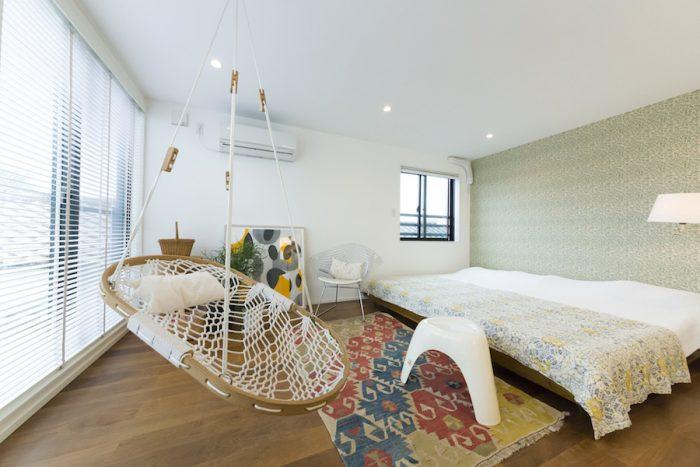 ウイリアム・モリスの壁紙がやわらかさを添える3階のベッドルーム。アメリカ製のハンモックは子供たちもお気に入り。