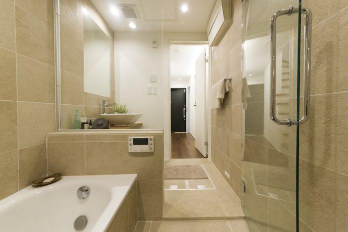 ガラス張りでホテルライクなバスルーム。凹凸のある素材感が気に入り、セラミックタイルを採用した。